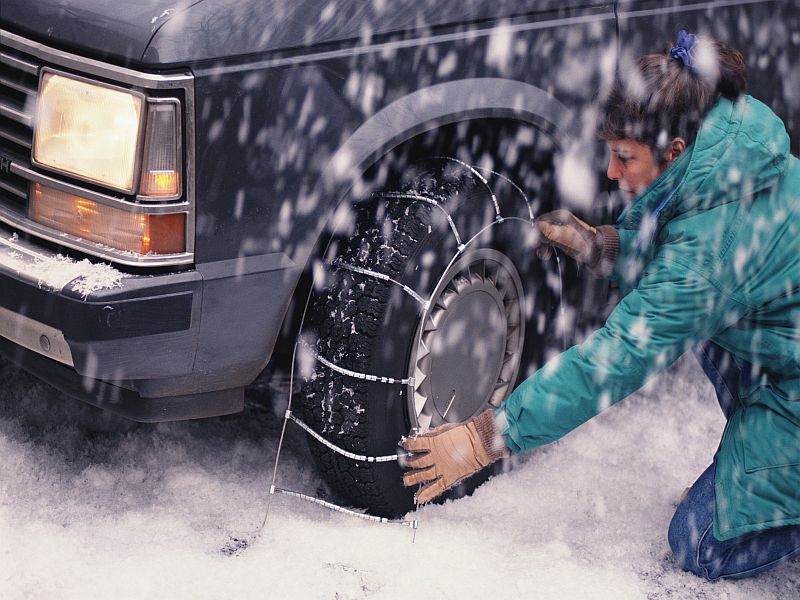 A woman putting tire chain on her car wheels in the snow