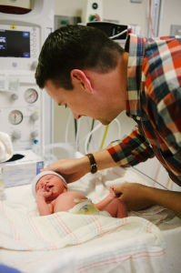 Man standing over newborn baby