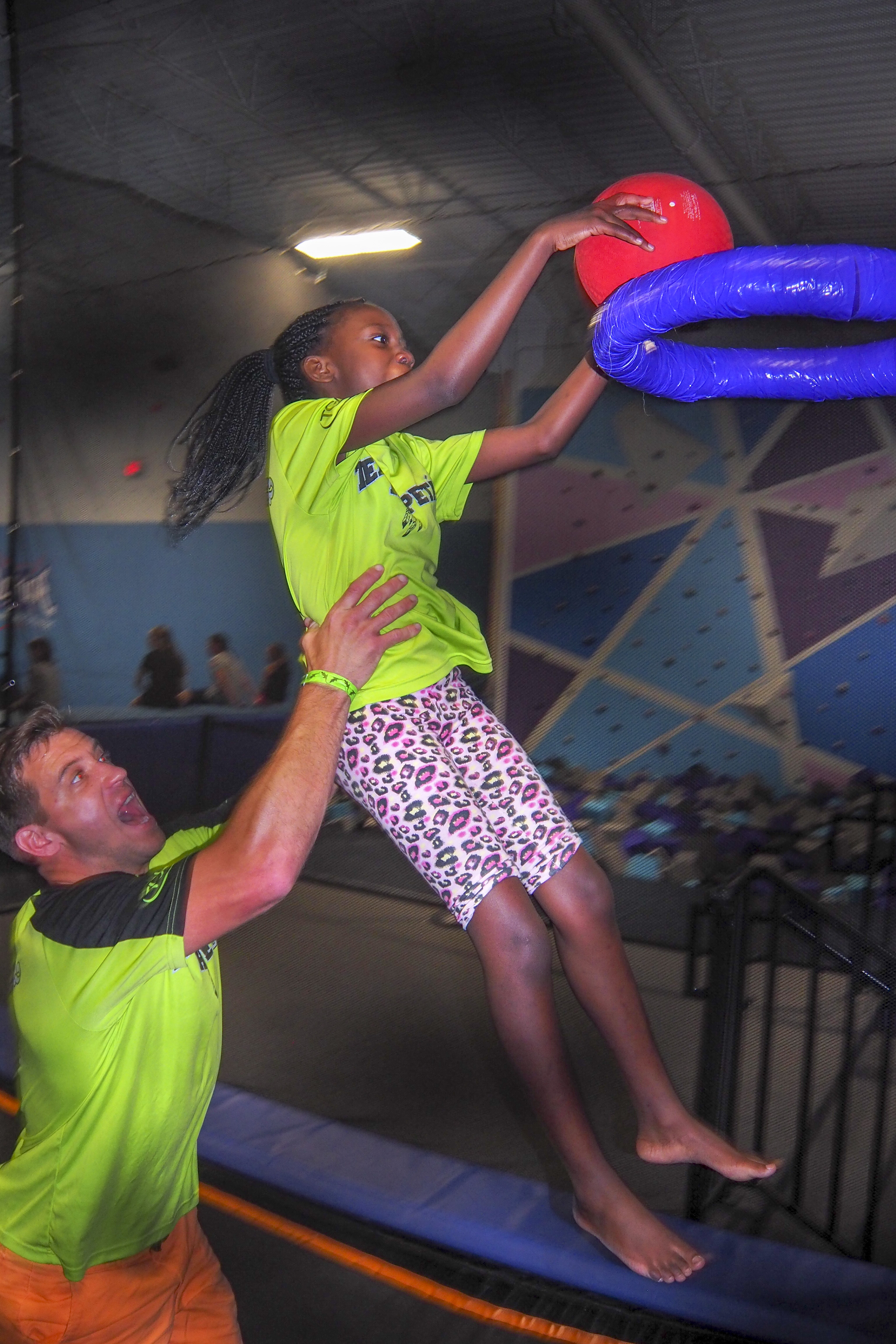 Young girl getting a lift on dunking a basketball