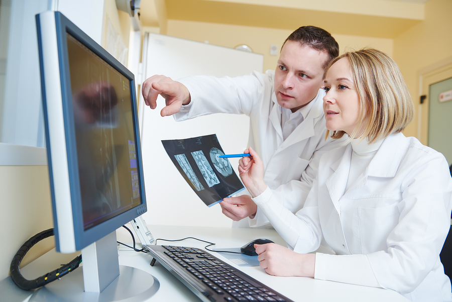 Male and female physicians looking at diagnostic imaging results