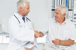Cancer doctor shaking hands with a senior patient