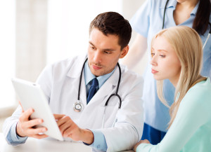 Oncology doctor showing larynx cancer symptom information to a patient on a tablet computer