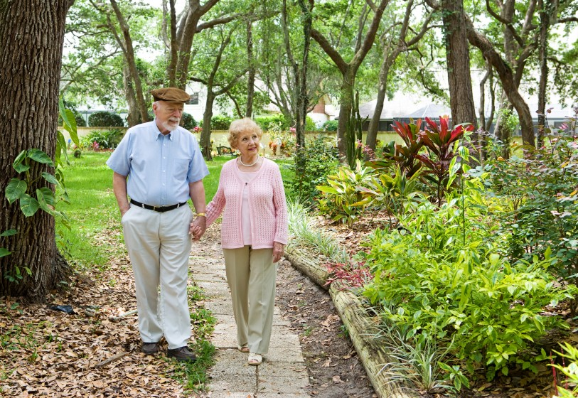 An elderly couple walking through a garden
