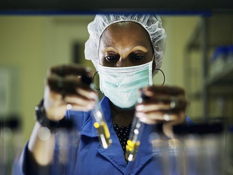 Woman examining two test tubes