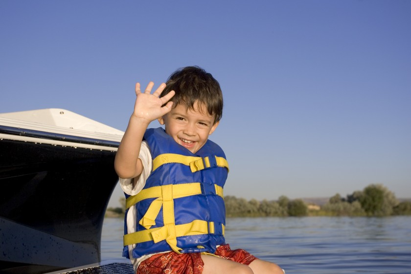 A child wearing a life jacket on a boat