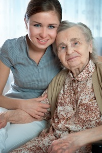 Elderly woman posing for camera with her nurse