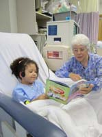 Girl reading book with grandma while receiving dialysis