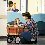 Nurse talking to little girl in a wagon