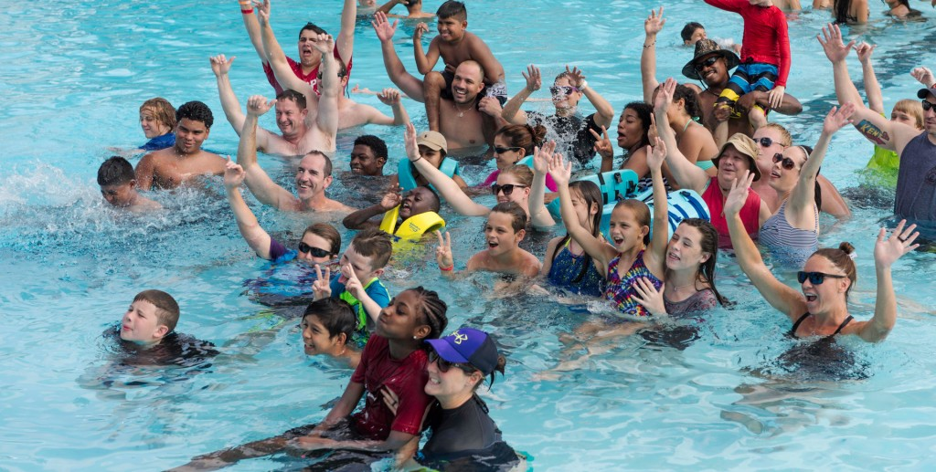 A group of adults and children raising their hands in a pool