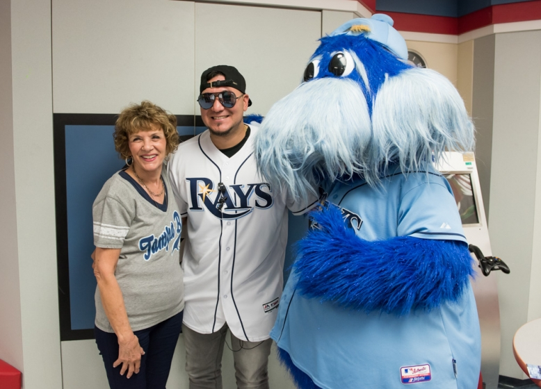 Tampa Bay Rays baseball player posing with a woman and the Rays' mascot