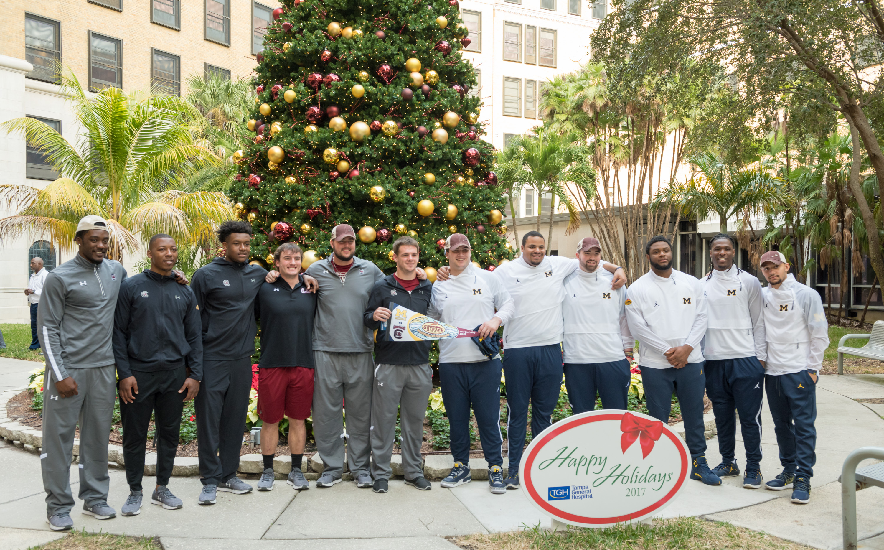 Outback bowl players in front of the Christmas tree