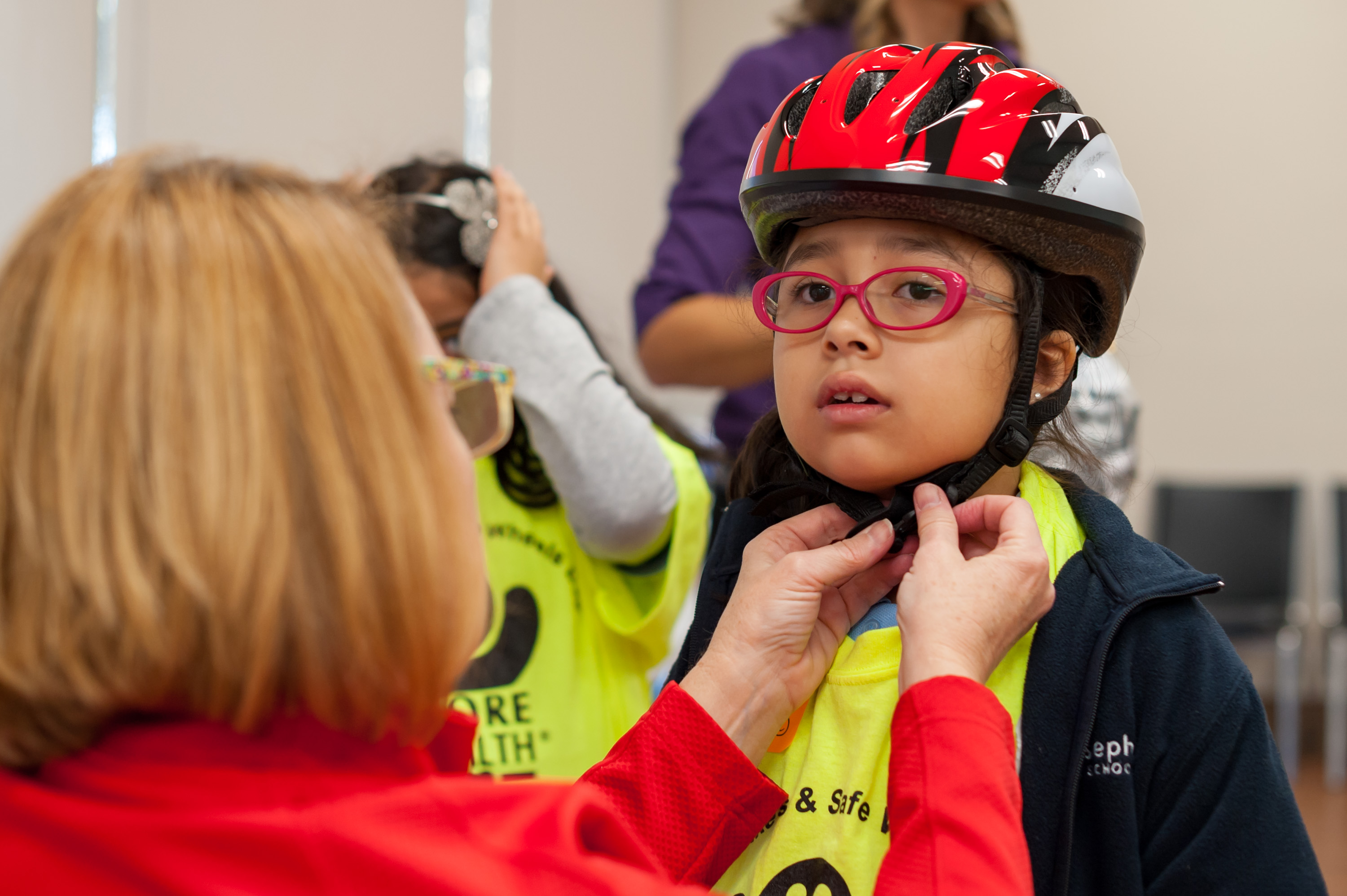 Girl trying on a helmet with More Health