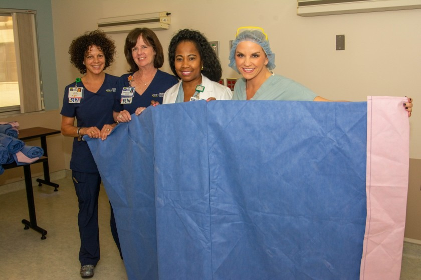 Tampa General team members hold up a sleeping bag made from recycled surgical materials.