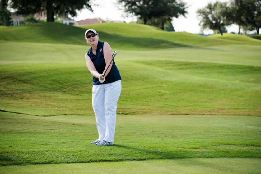An elderly woman golfing