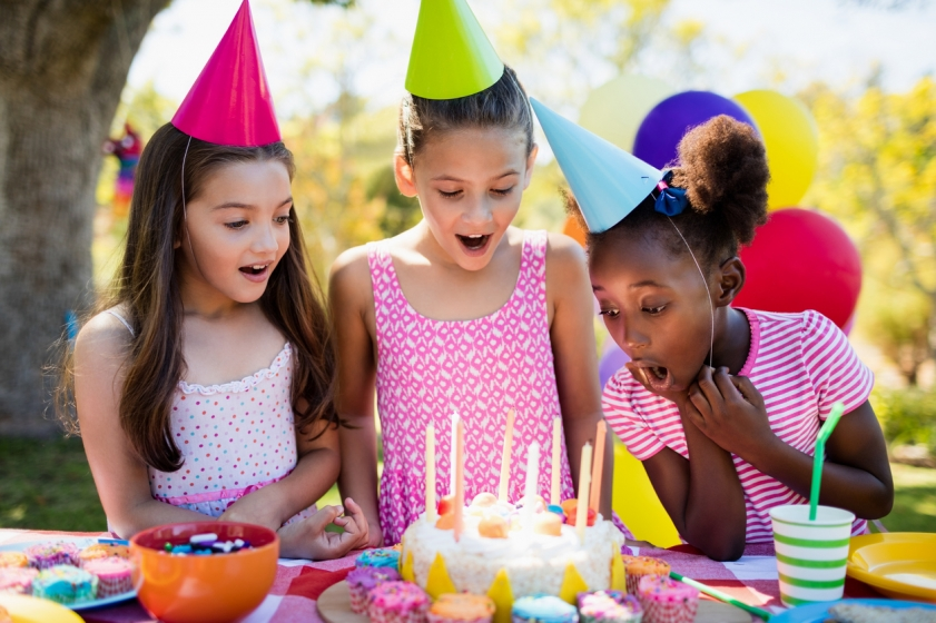 Two girls watching another girl blow out the candles on a birthday cake