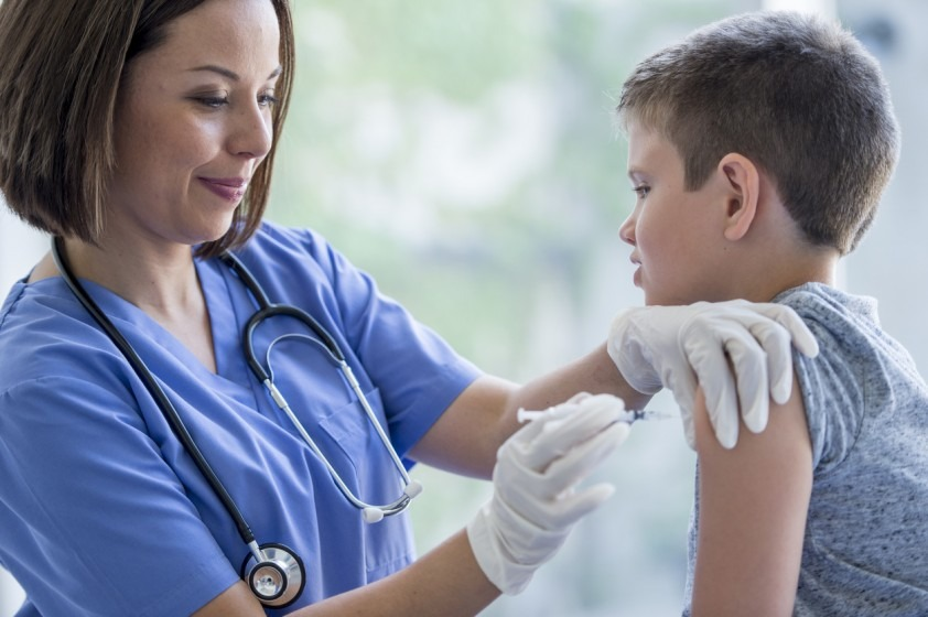 Boy about to receive vaccination shot from nurse