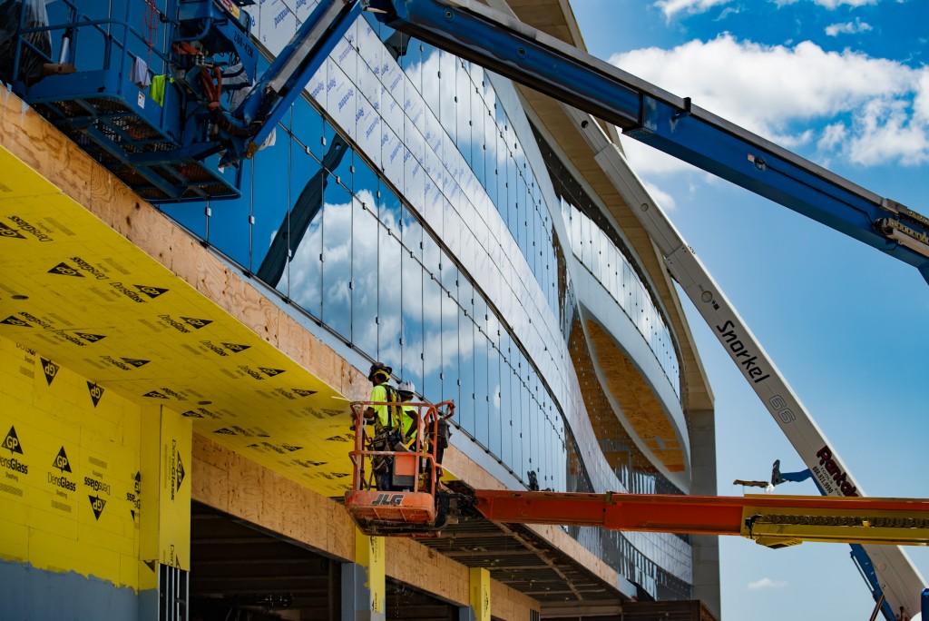Workers use lift cranes to finish the exterior of the TGH Brandon Healthplex.