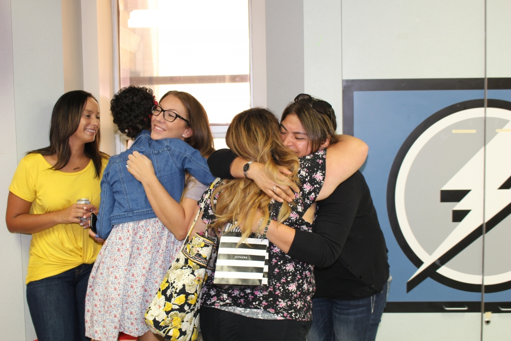 Group of girls hugging after ringing the chemo bell