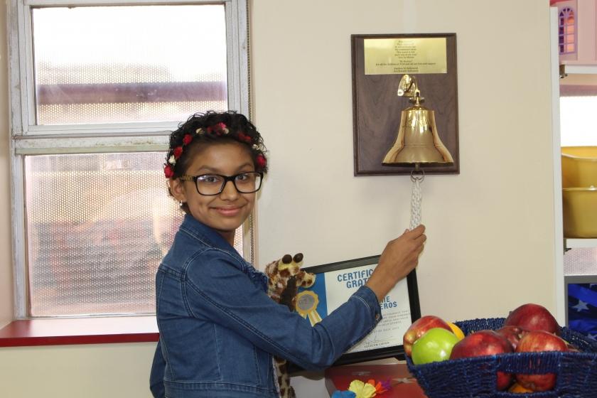 Teen girl ringing the chemo bell