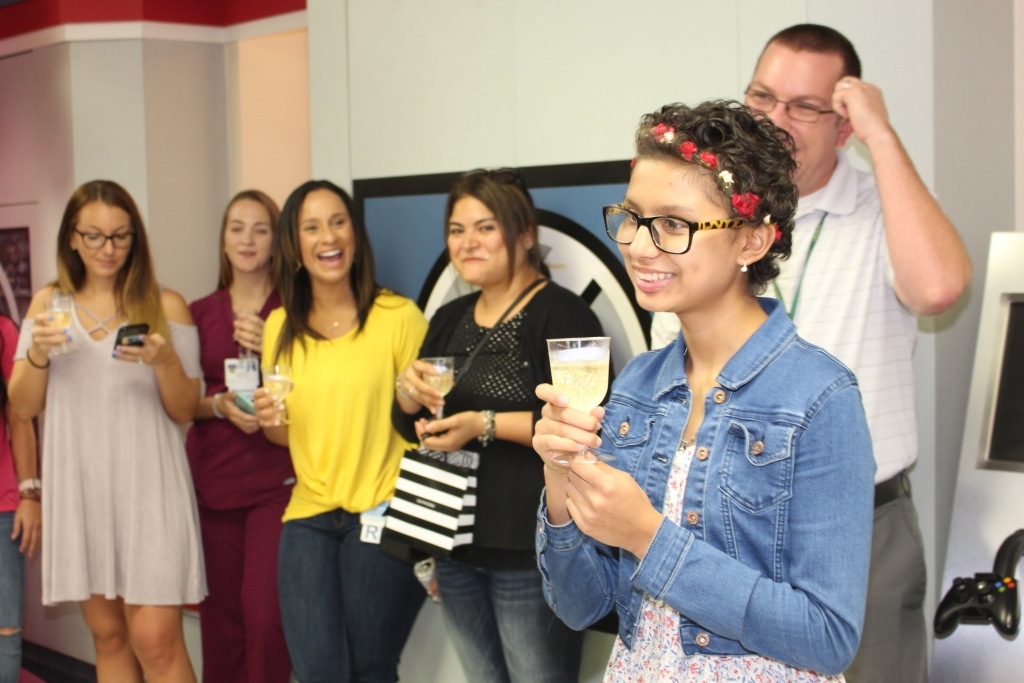Group of people toasting to a teen girl ringing the chemo bell