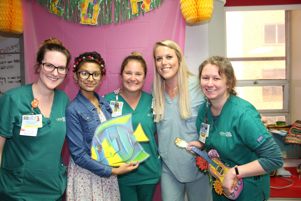Teen girl posing with physicians after ringing the chemo bell