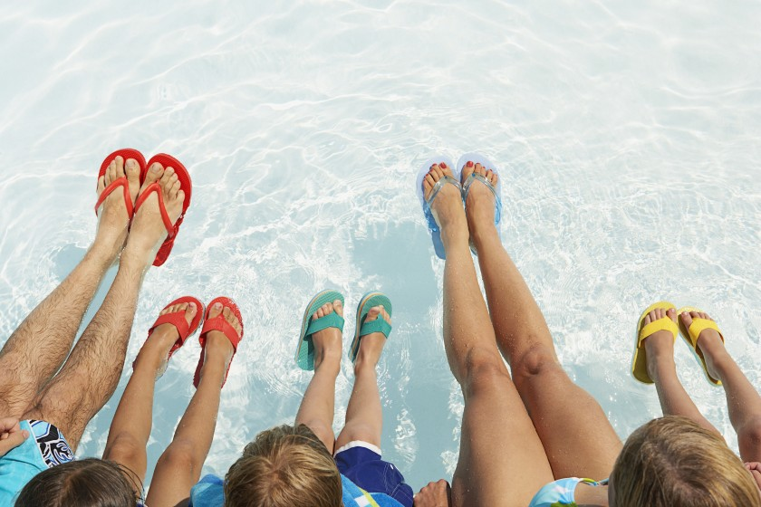 A family of four wearing flip flops