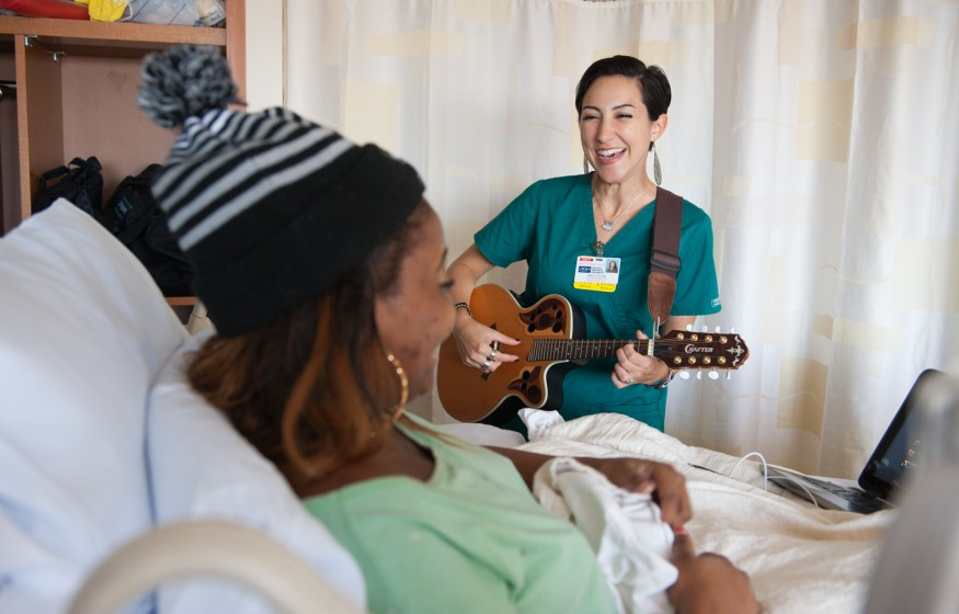 Nurse plays guitar to patient who lays in hospital bed