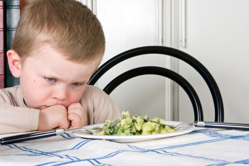 A young boy looking at broccoli angrily