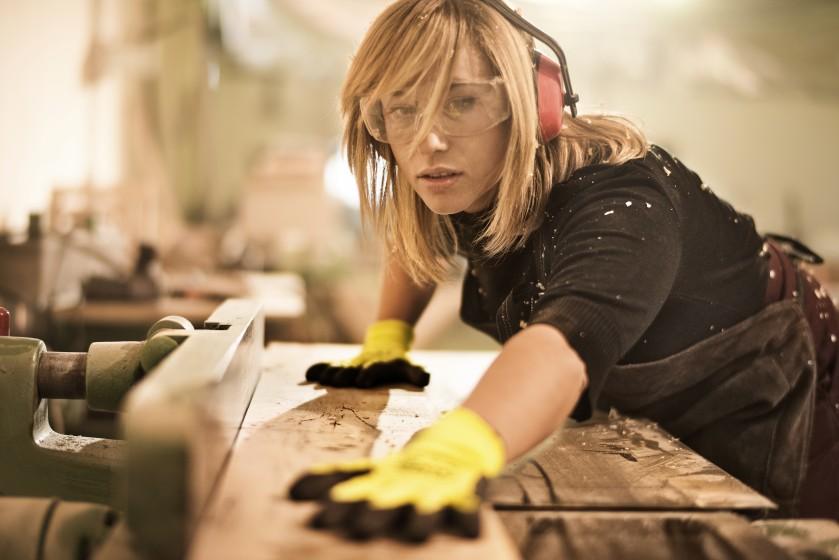 Woman using an electric wood saw