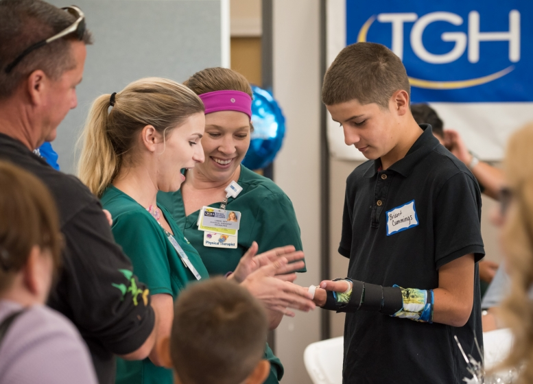 Two physical therapists looking at a young boy's injured arm at the trauma awareness luncheon