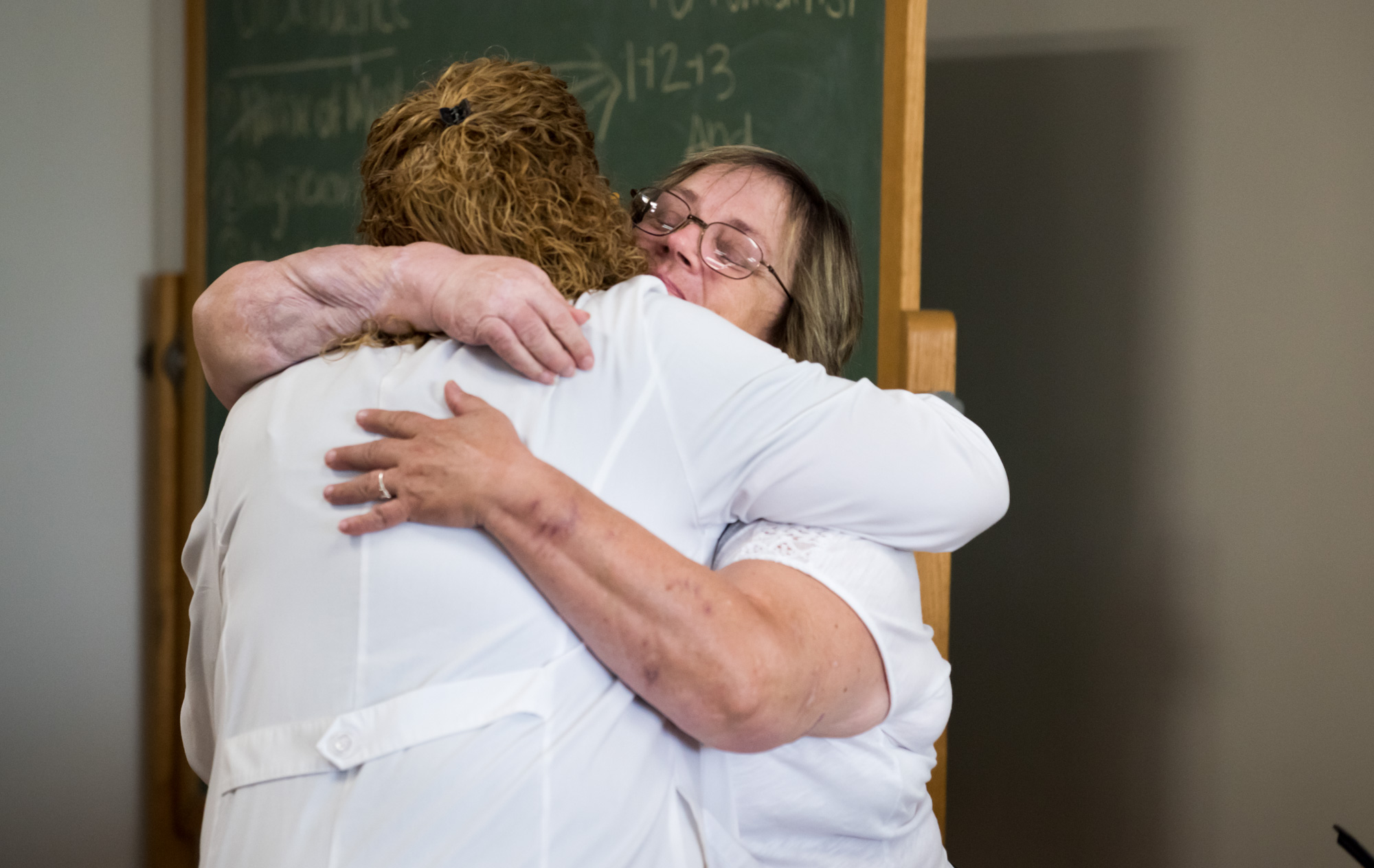 A female physician hugging a female patient at the trauma awareness luncheon