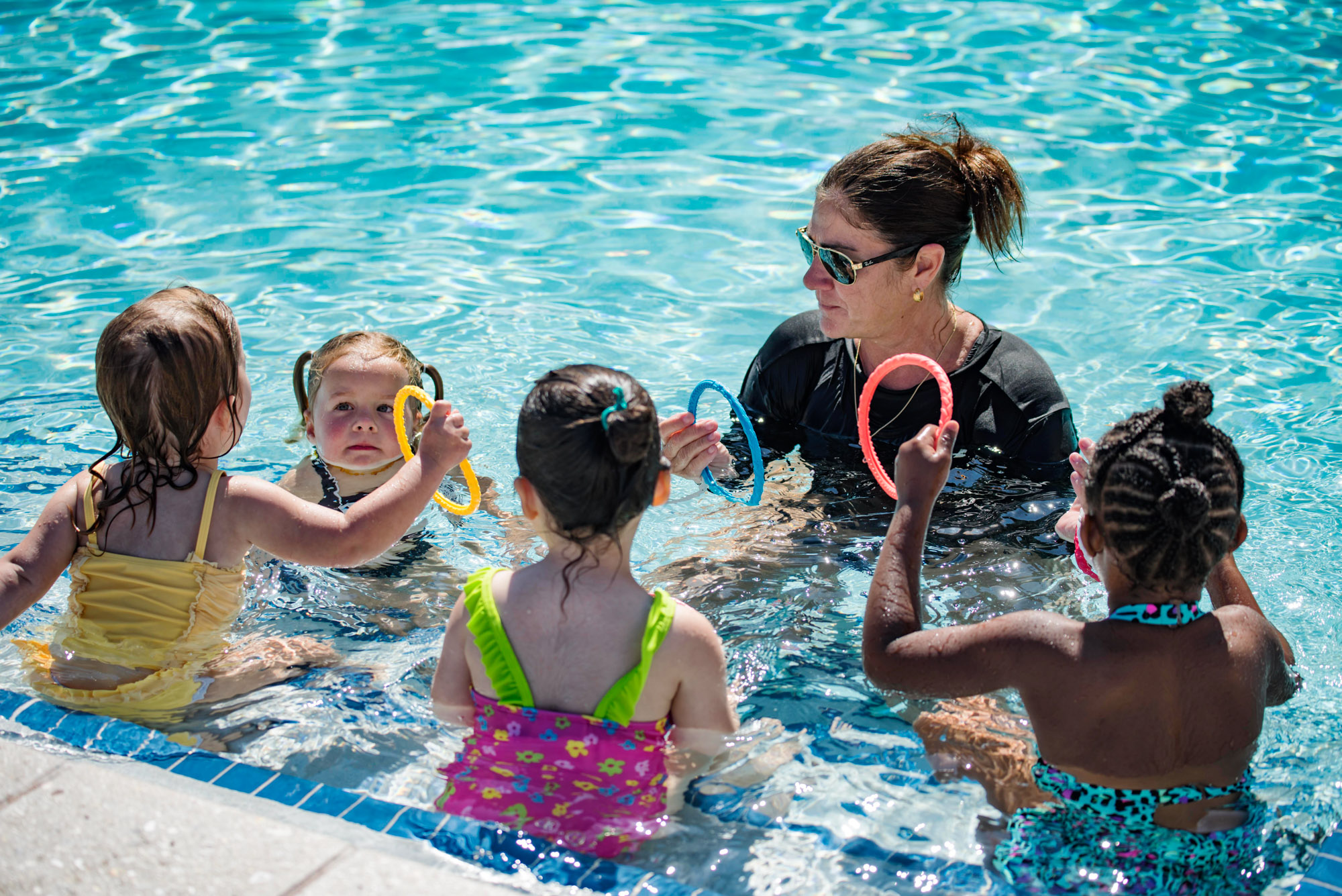 Woman teaching a group of young girls how to swim