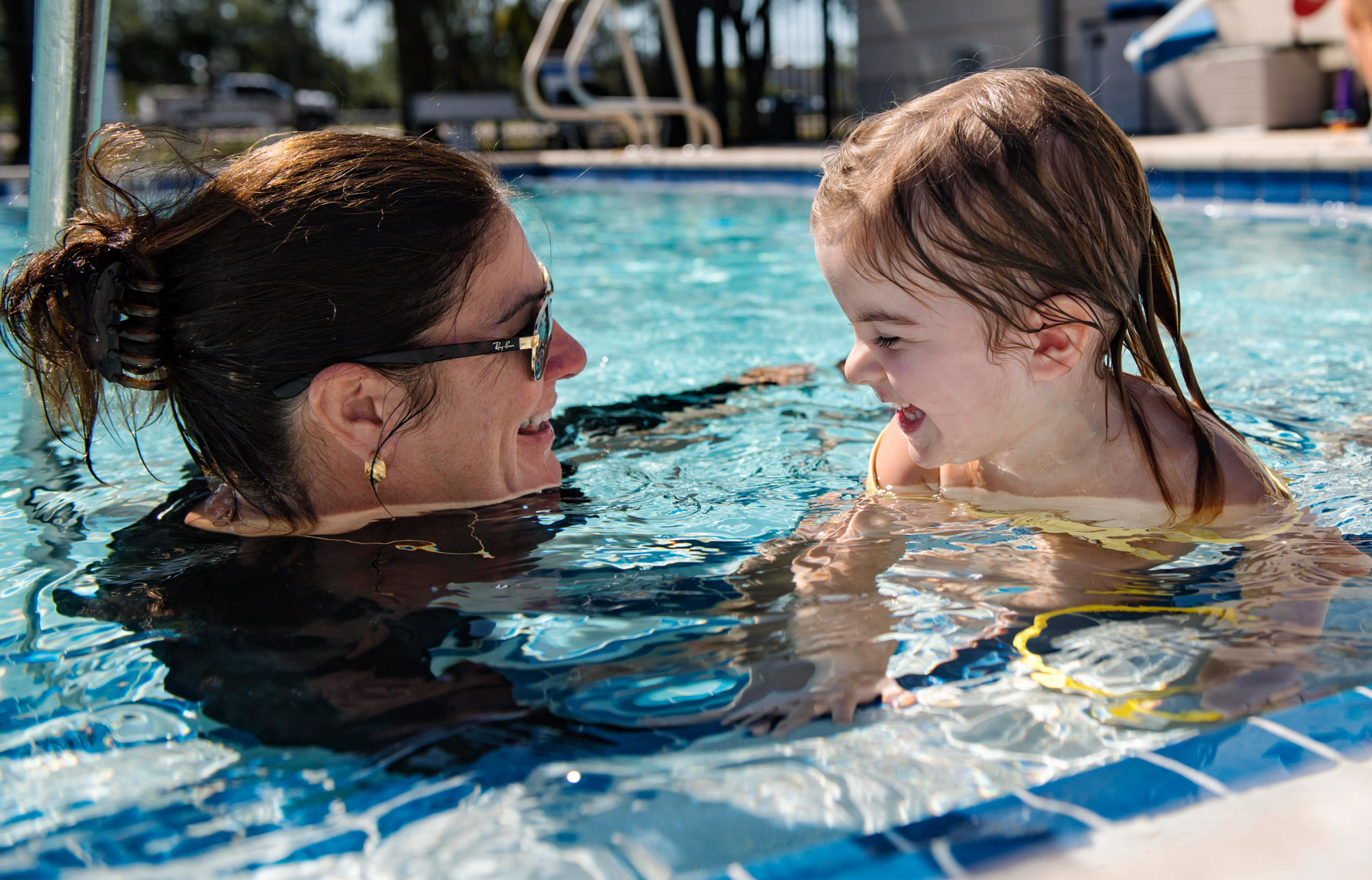 Woman teaching a young girl how to swim