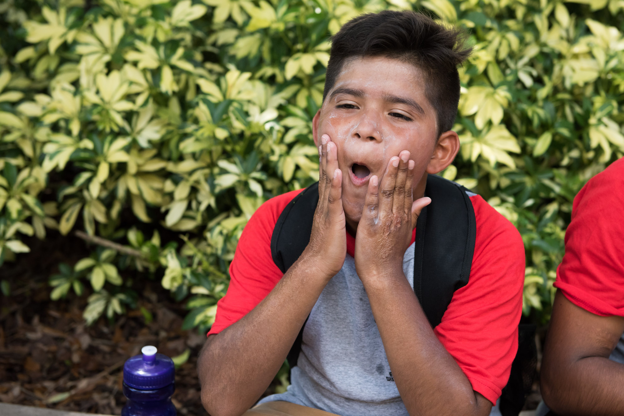 Young boy applying sunscreen at Busch Gardens with Camp Hopetake