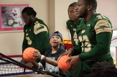 USF football players playing basketball with patients