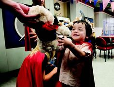 Benjamin Ramroop, three, grabs a stuffed bear as employees from Bristol-Myers Squibb donned superhero capes to visit our patients and deliver two hundred and fifty stuffed bears.