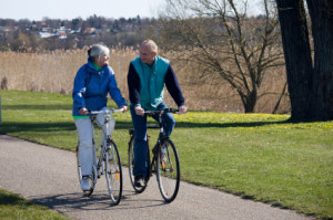 An elderly couple riding bikes outside