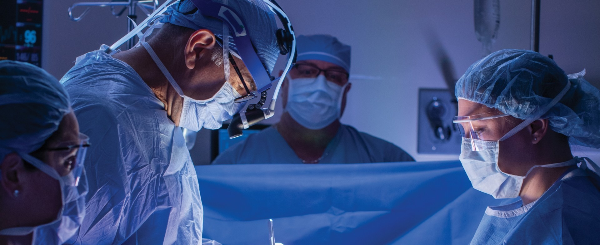 two surgeons, a nurse, and an anesthesiologist performing surgery