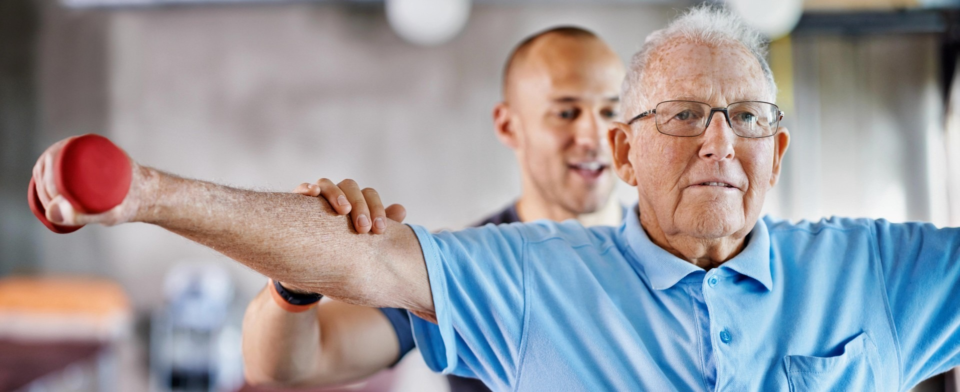 Physical therapist helping elderly man with shoulder presses