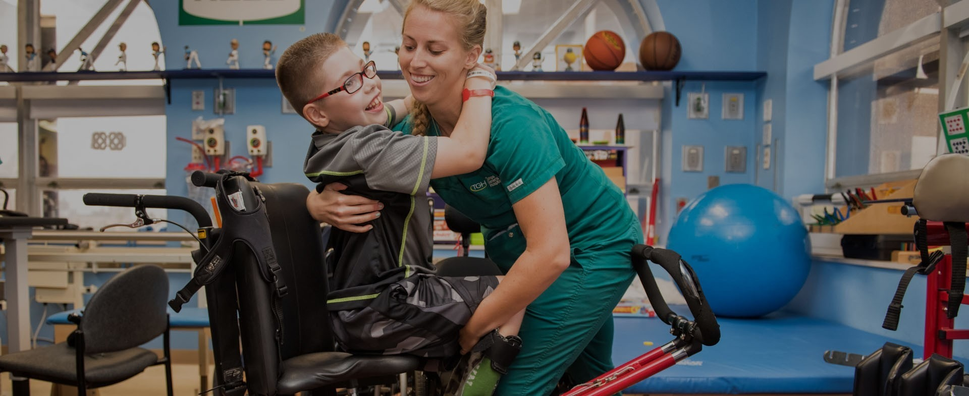 A therapist helping a child out of a wheelchair