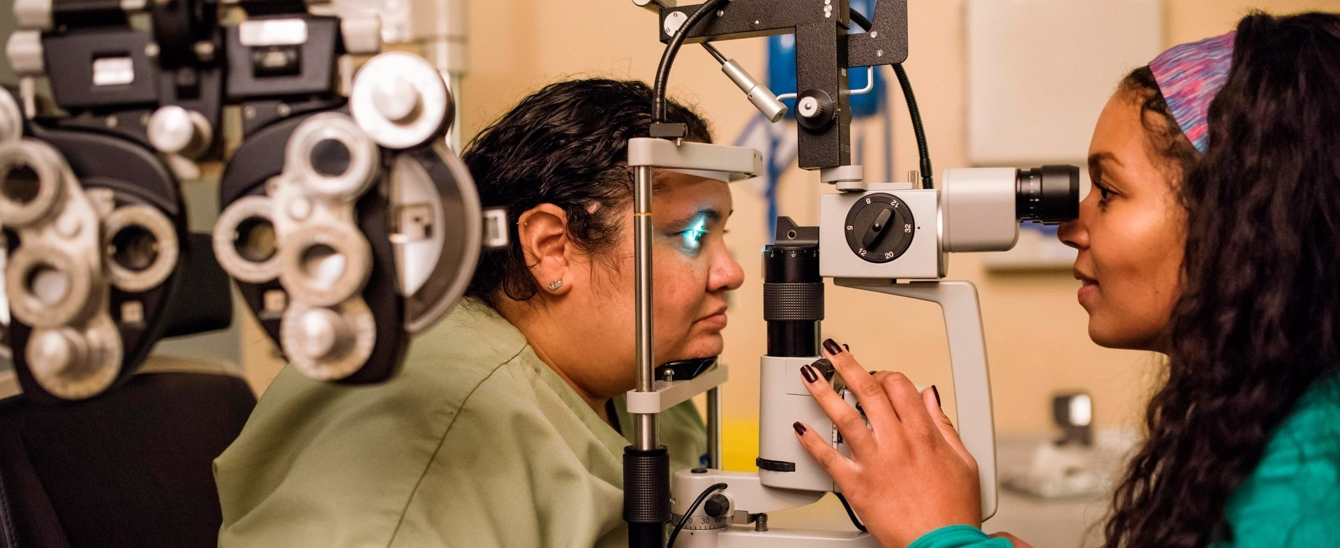 Woman physician checking the eyes of a female patient