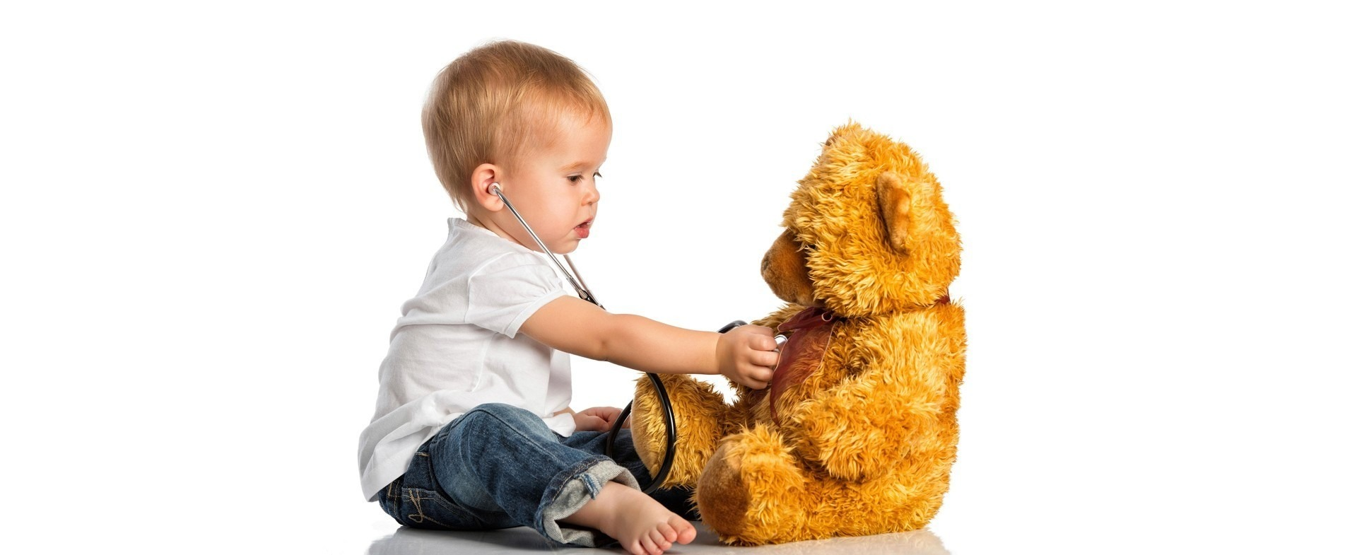 Toddler using a stethoscope to listen to teddy bear's heart