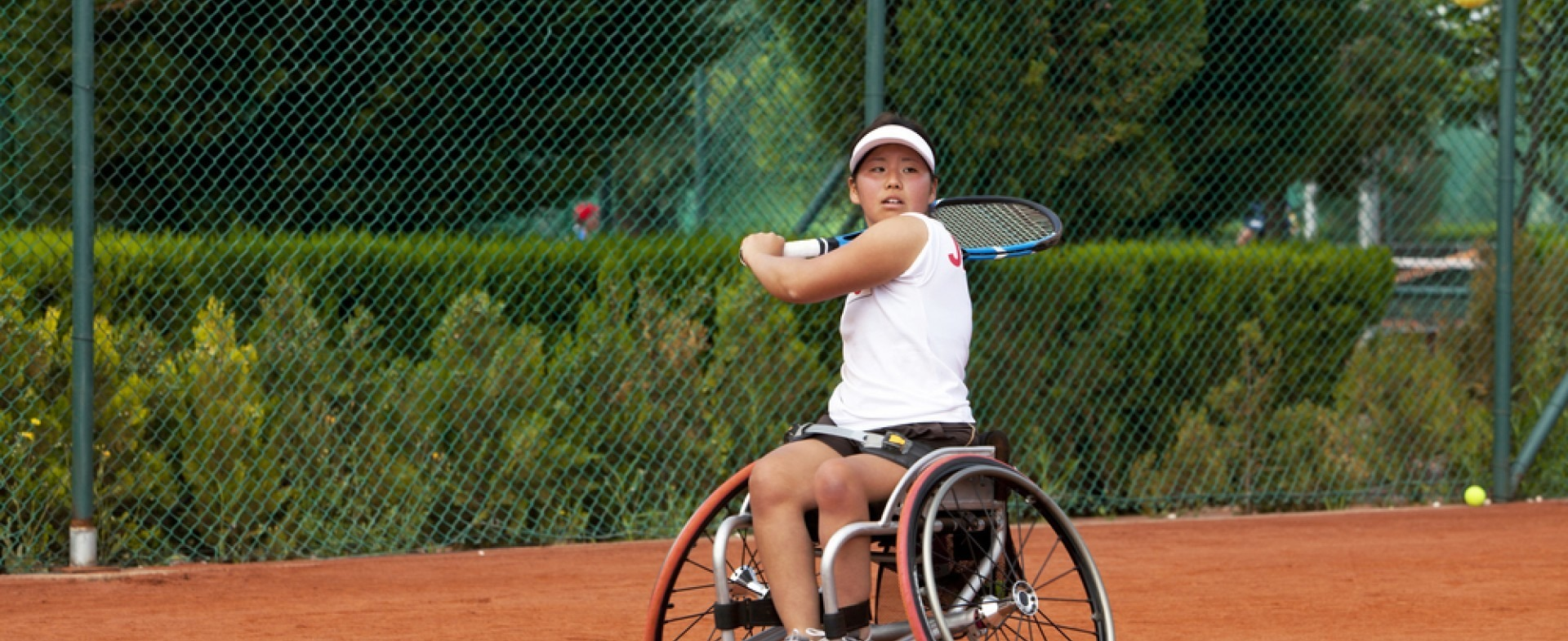 Woman playing tennis in a wheelchair