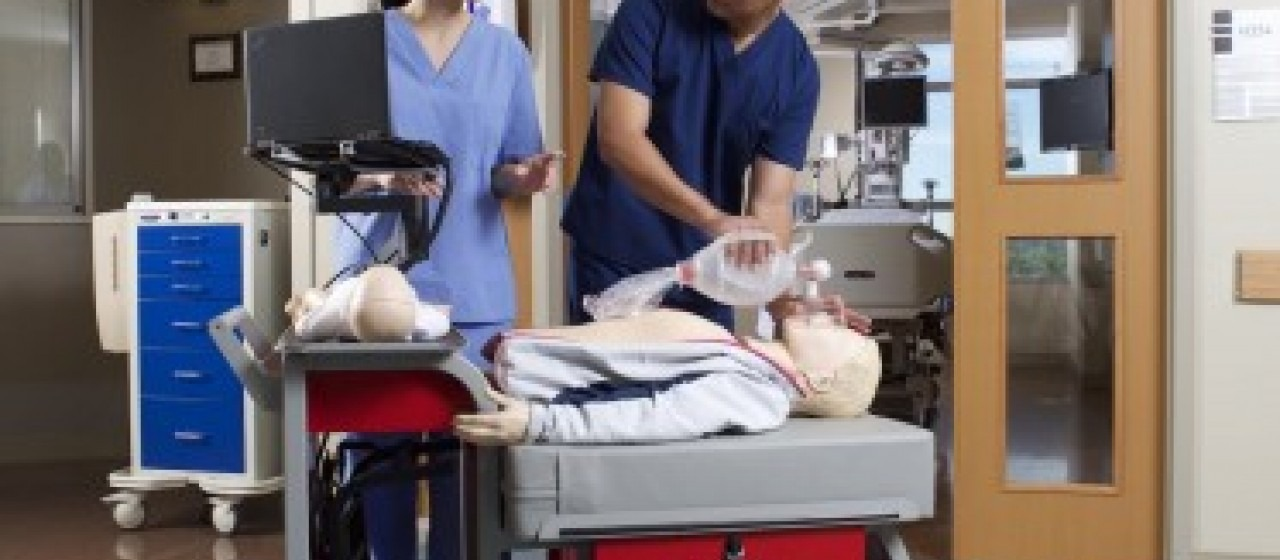 Man providing bag ventilation to a dummy while an instructor watches