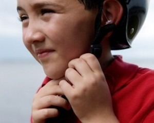A boy taking off his bicycle helmet