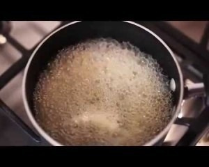A pot with boiling liquid on the stove top