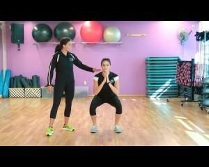 Two women stretching in a gym