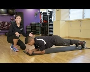 A man doing a plank with a trainer