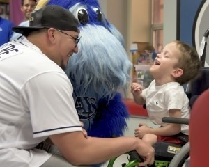 Tampa Bay Rays baseball player laughing with a young male patient