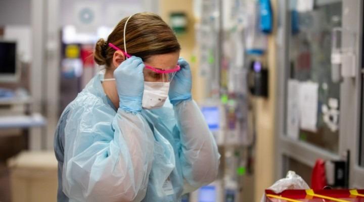 COVID unit physician putting on her PPE
